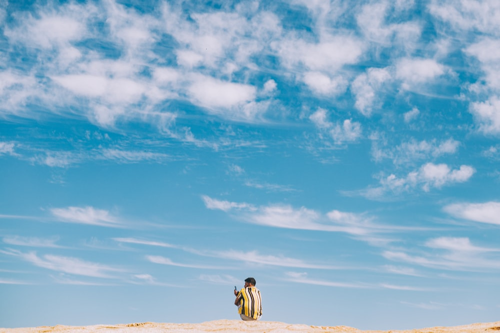 man and woman walking on brown sand under blue sky and white clouds during daytime