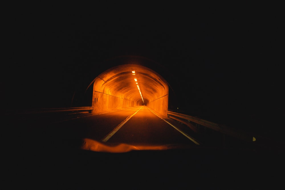 person in black jacket standing on tunnel during nighttime