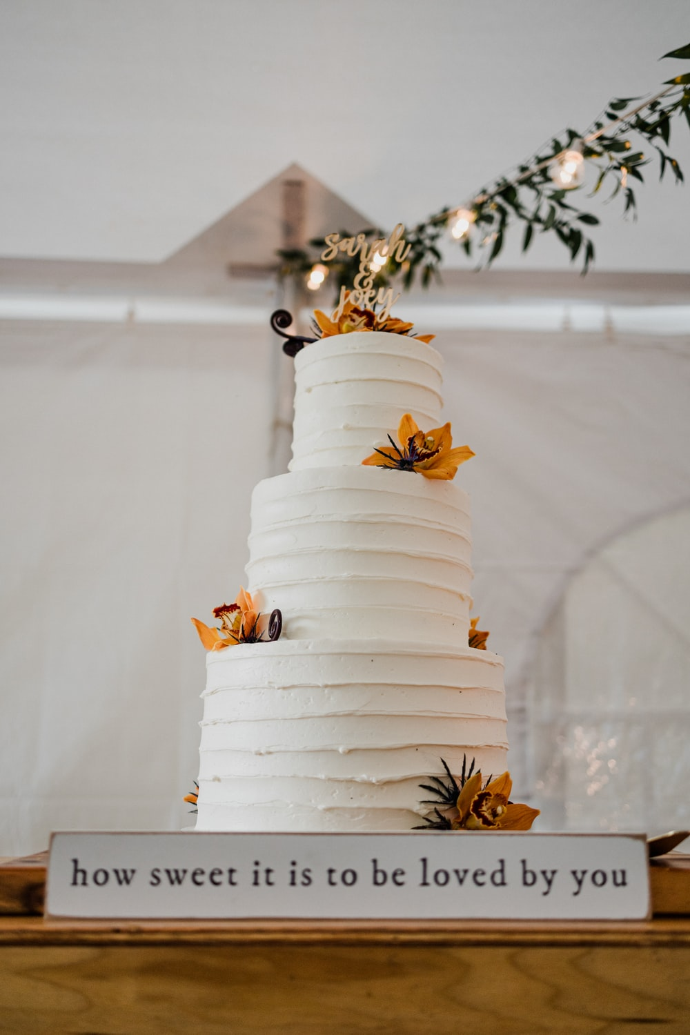 white 4 tier cake with yellow flowers on top