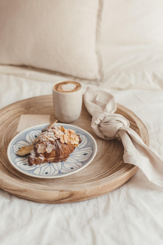 brown bread on white ceramic plate beside white ceramic mug on brown wooden table