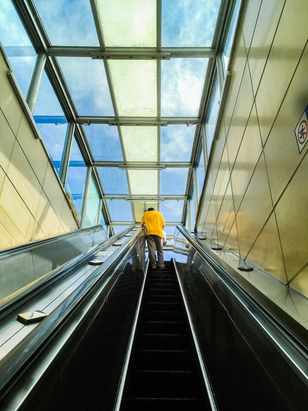 person in yellow jacket walking on escalator