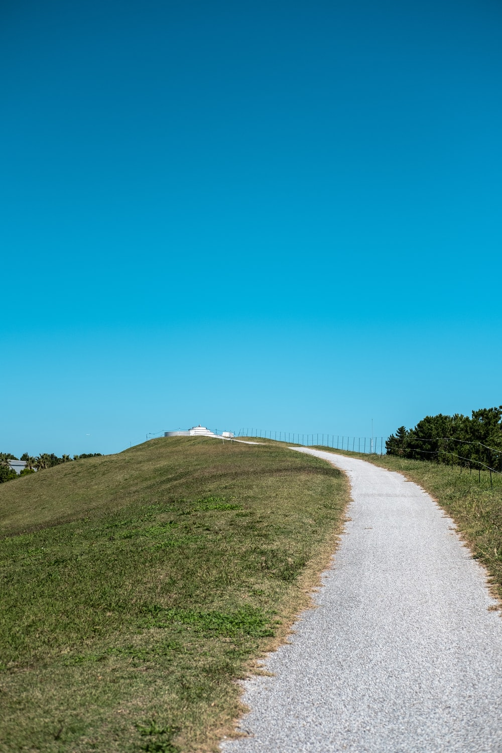 gray road between green grass field under blue sky during daytime