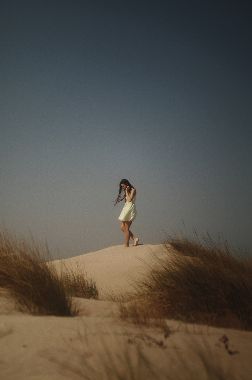 woman in white dress standing on brown field during daytime