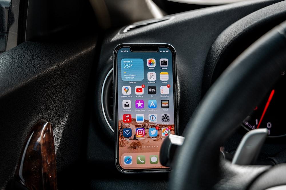 black iphone 4 on car dashboard