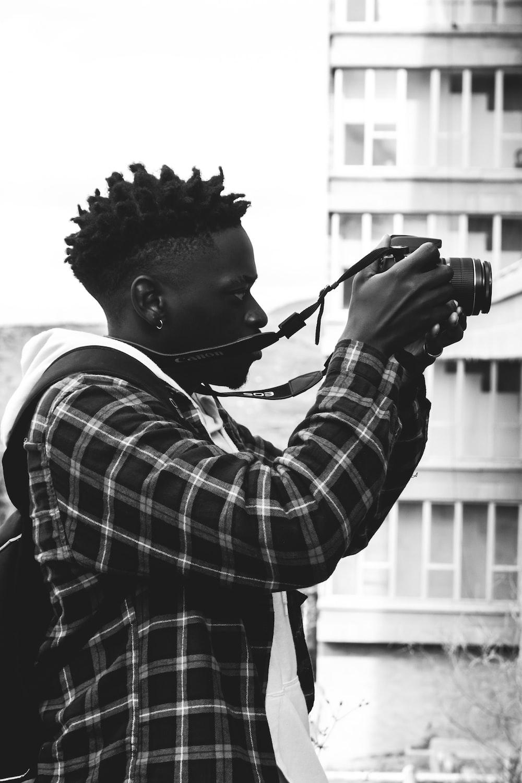 man in plaid shirt using dslr camera