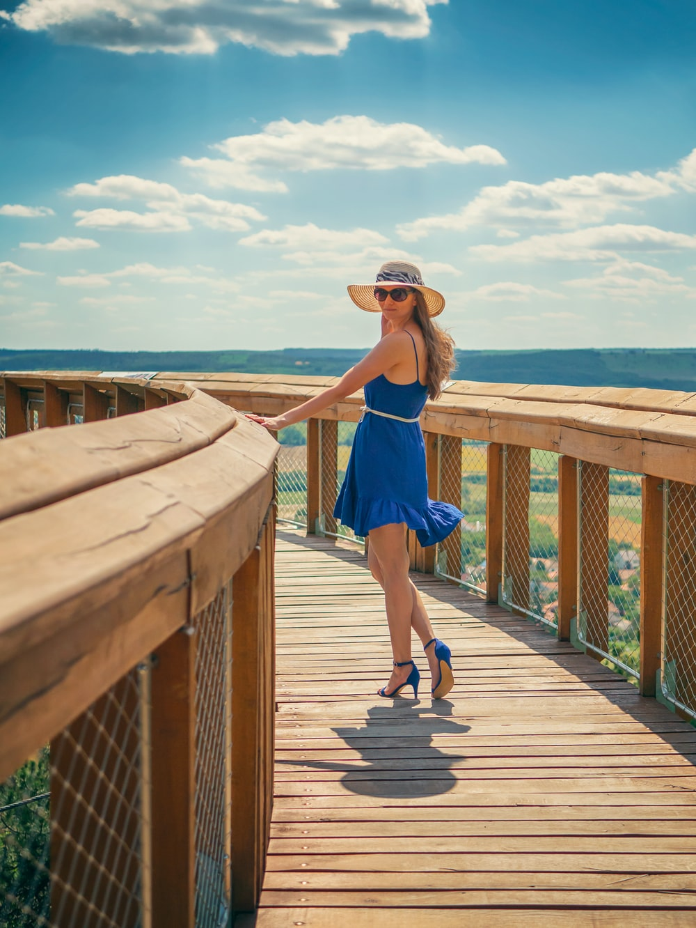 woman in blue tank top and blue shorts standing on brown wooden dock during daytime