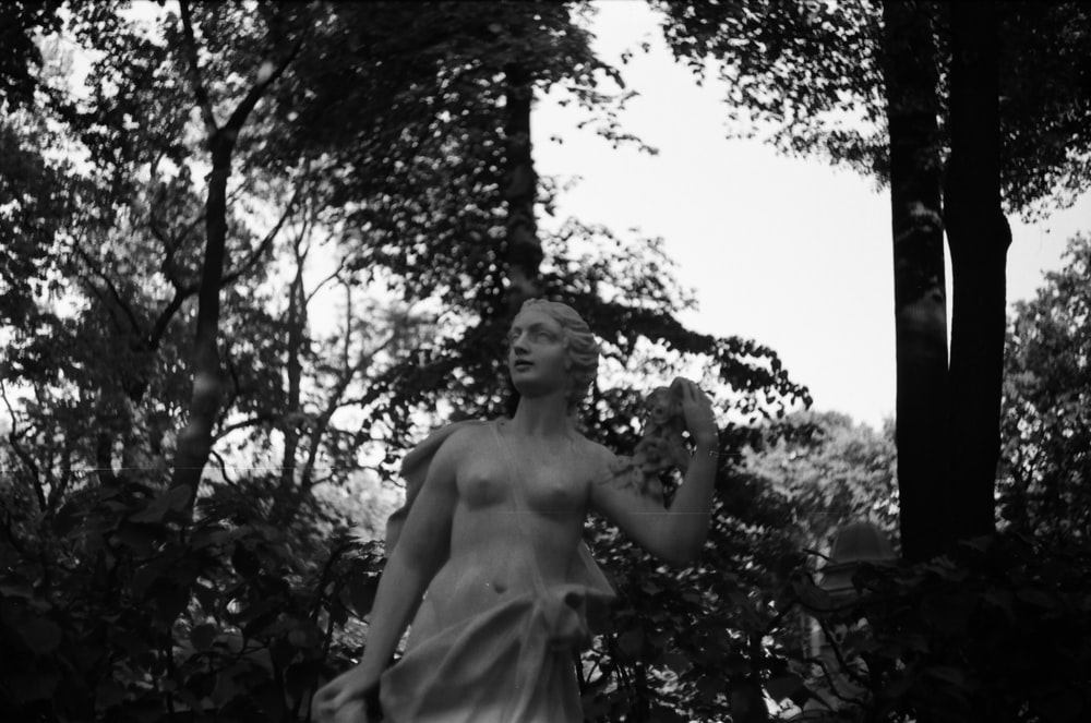 grayscale photo of topless woman standing near tree