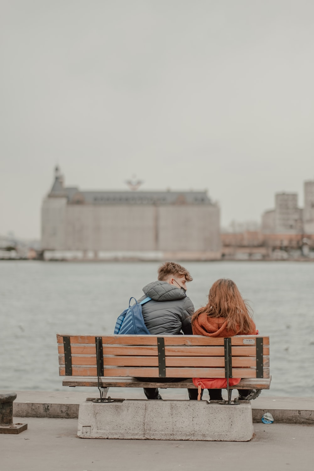 couple sitting on brown wooden bench near body of water during daytime