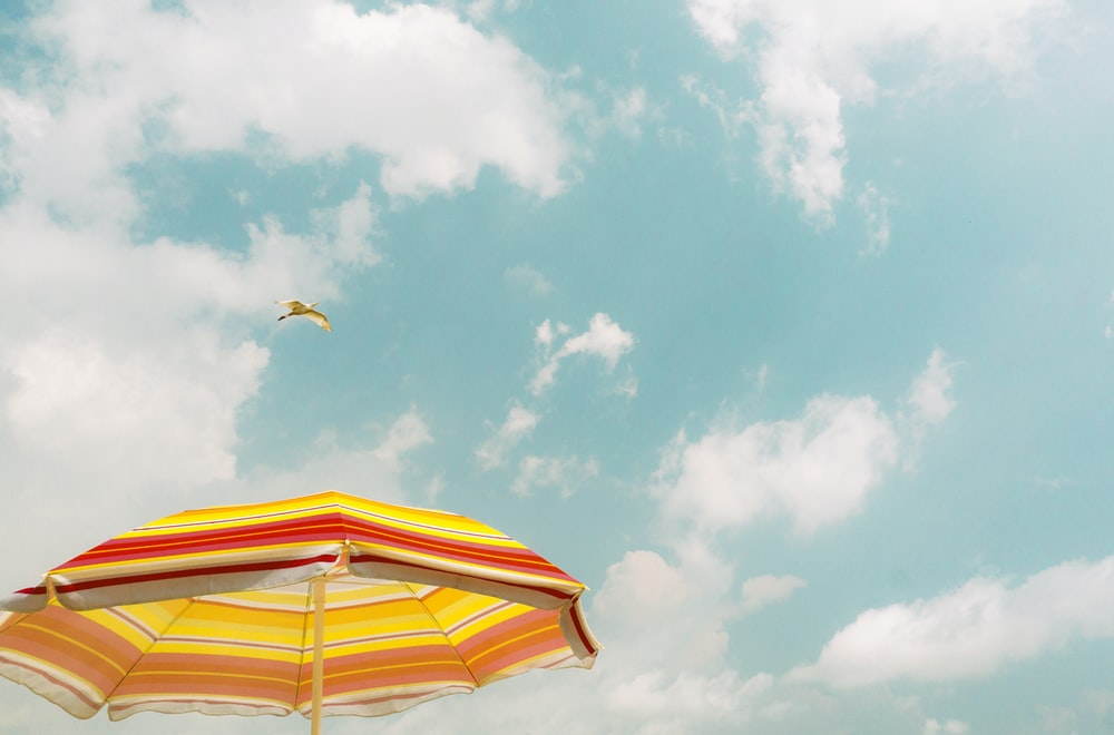 yellow and white umbrella under blue sky during daytime
