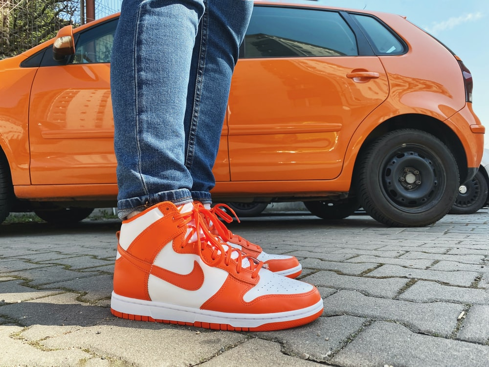 person in blue denim jeans and red nike sneakers standing beside orange car