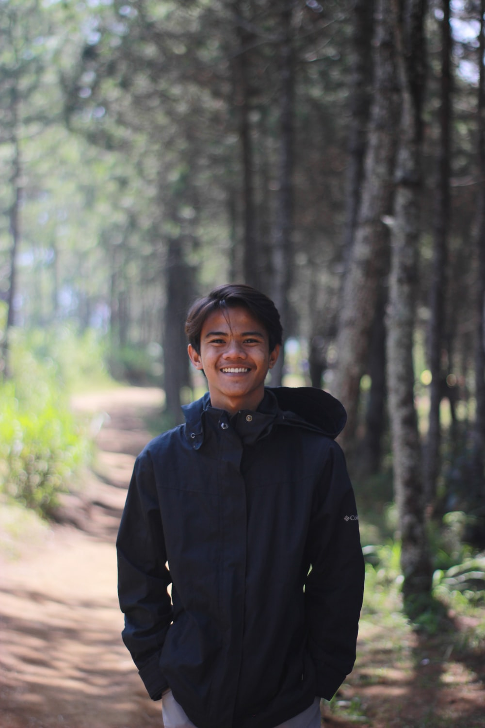 man in black jacket standing in forest during daytime