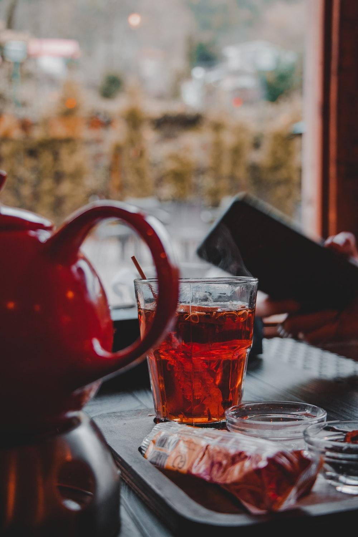 clear glass mug with brown liquid on table
