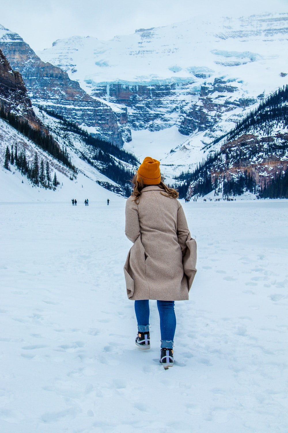 woman in brown coat standing on snow covered ground during daytime