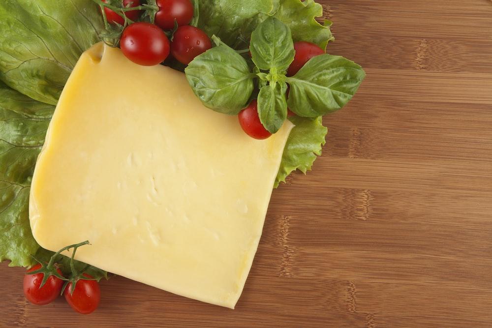 red tomato beside yellow cheese