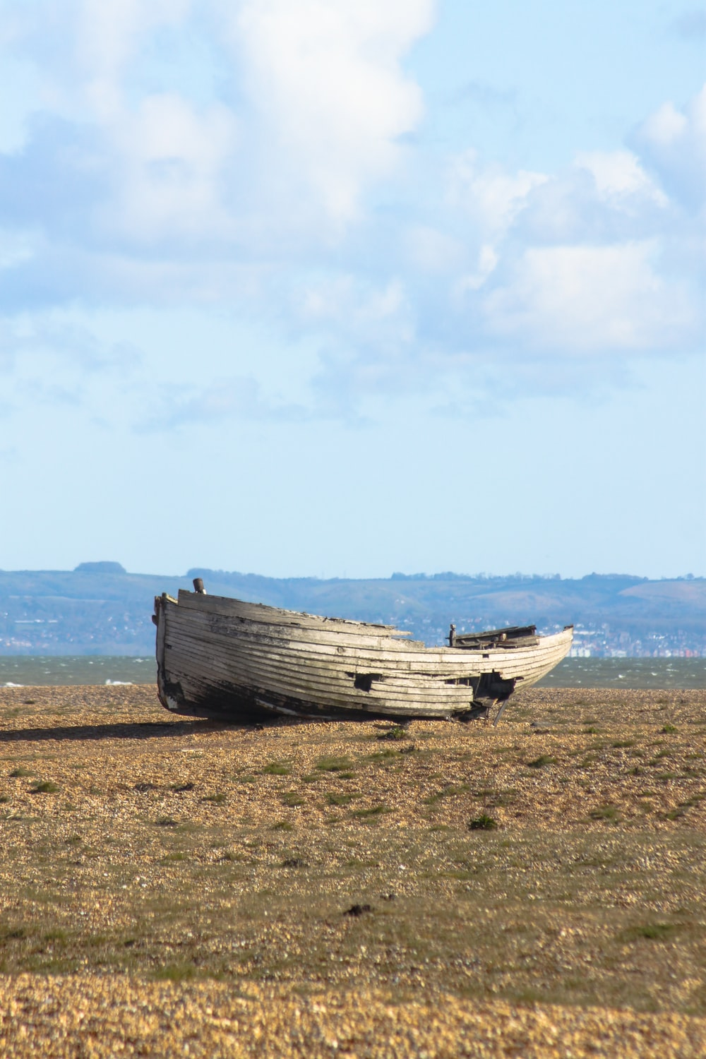 white boat on brown field under white clouds during daytime