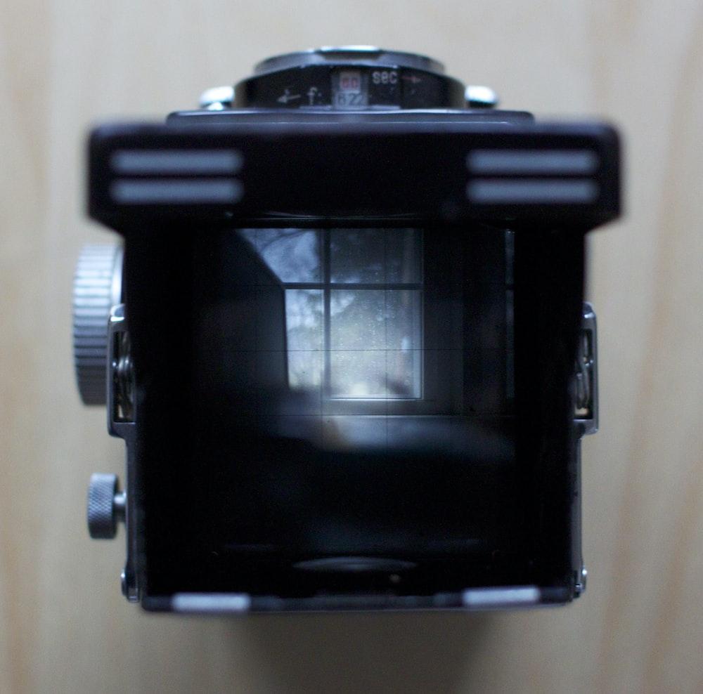 black dslr camera on white textile