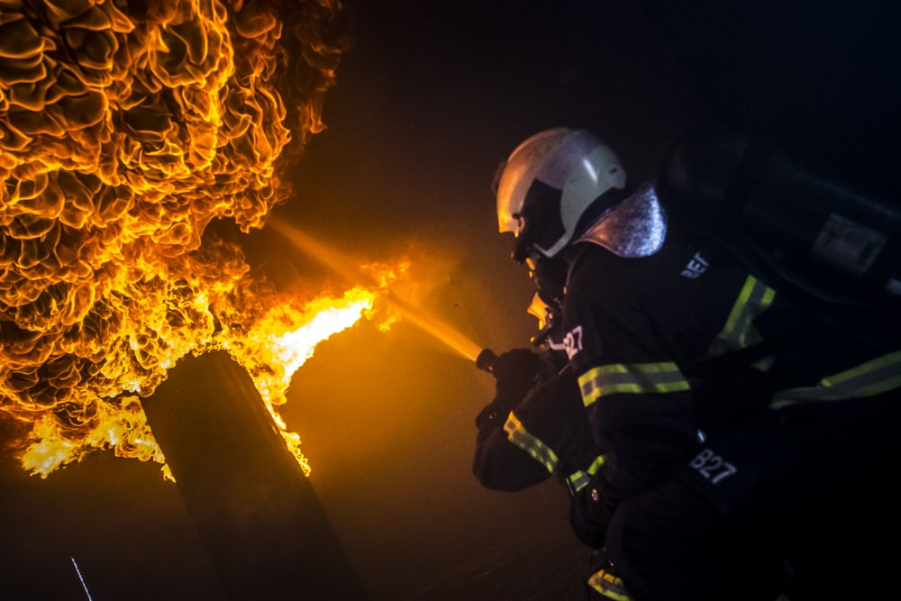 man in green and black jacket wearing helmet standing in front of fire