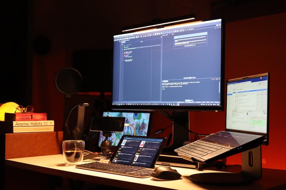 black flat screen computer monitor turned on beside black laptop computer