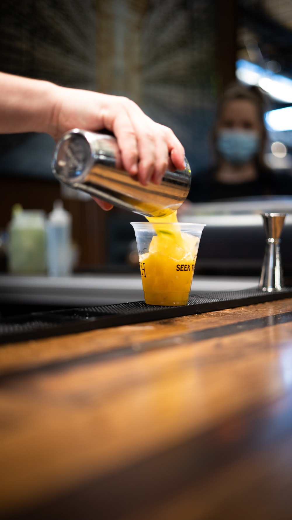 person pouring yellow liquid on clear drinking glass