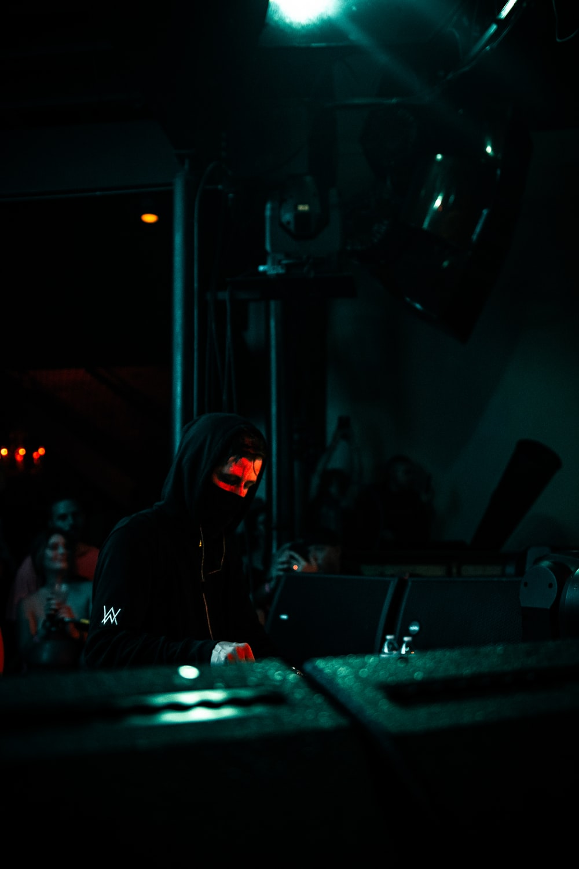man in black hoodie standing near stage