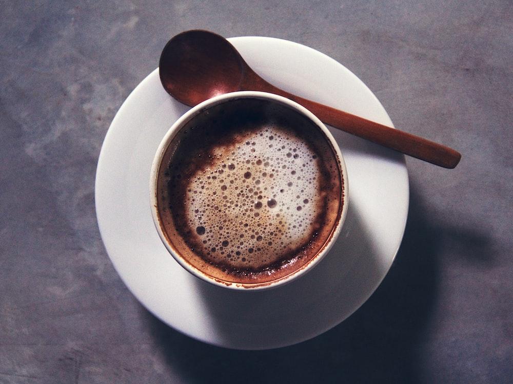 white ceramic mug with brown liquid inside
