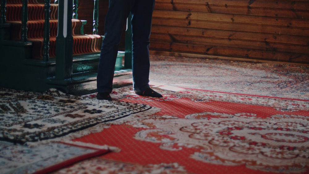 person in black pants standing on red and white floral area rug