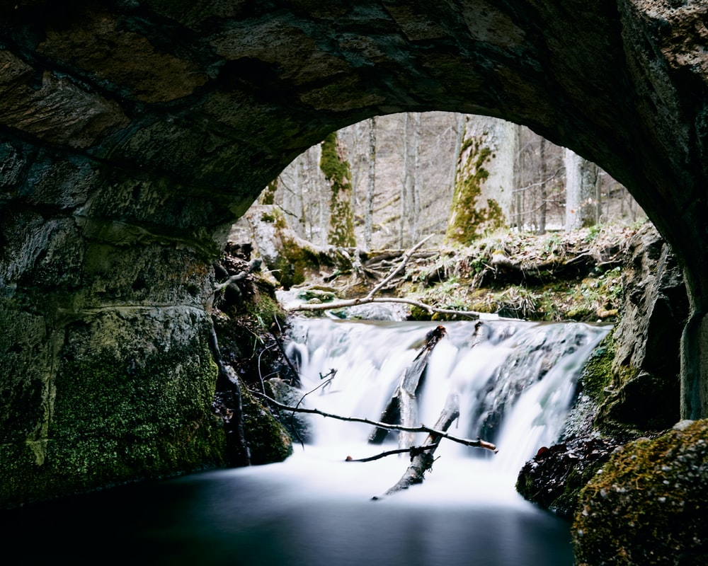 water falls under gray concrete arch bridge during daytime