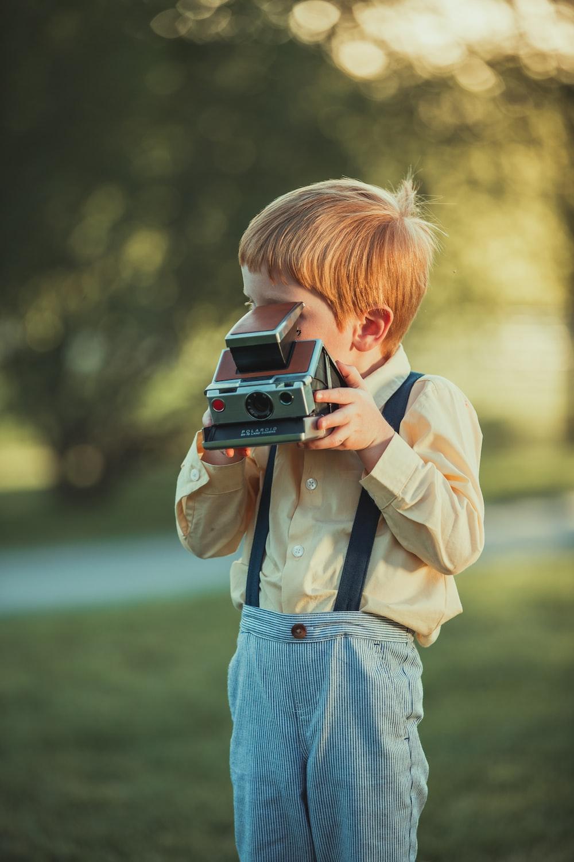 boy in beige jacket holding camera