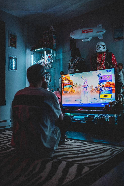 man in red shirt watching tv