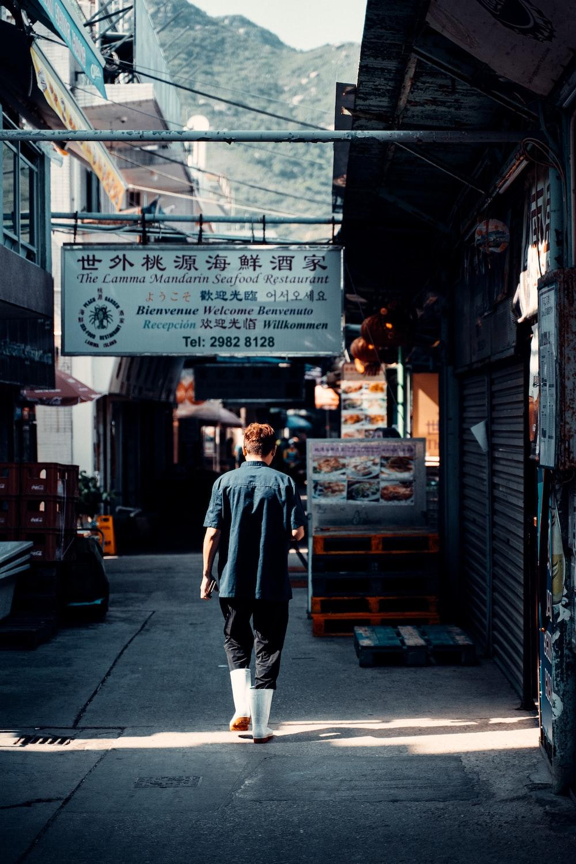 man in gray long sleeve shirt walking on street during daytime