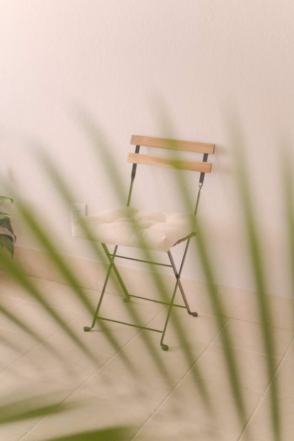brown wooden folding chair beside green and white wall