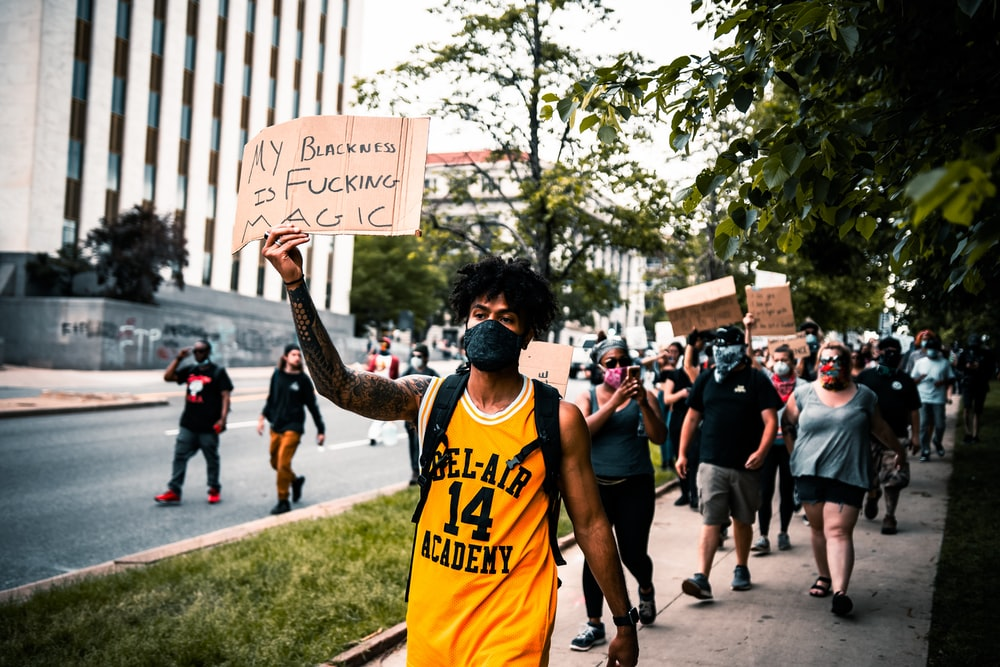 man in yellow tank top holding white and black signage