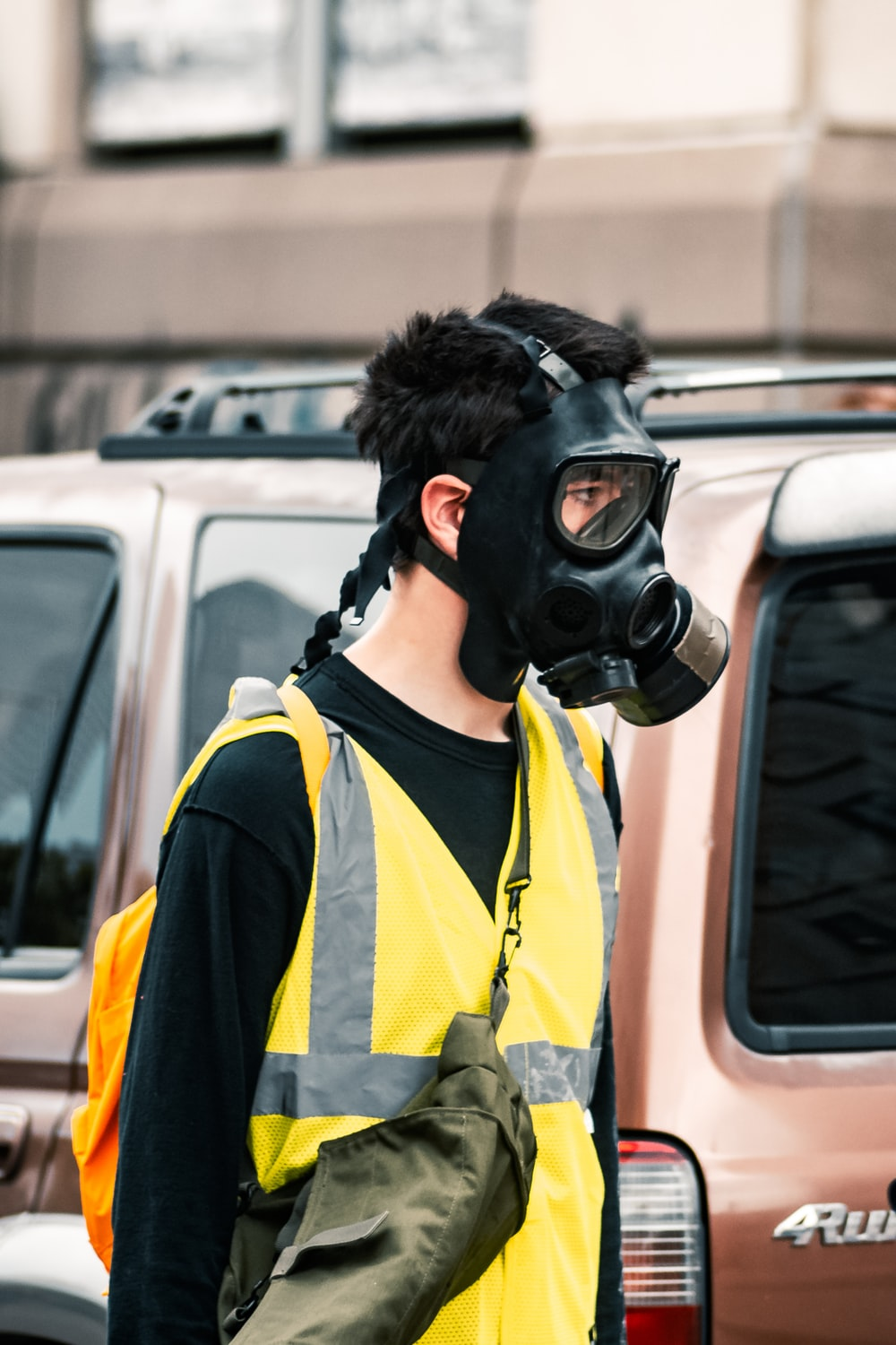 woman in yellow and black gas mask and yellow vest