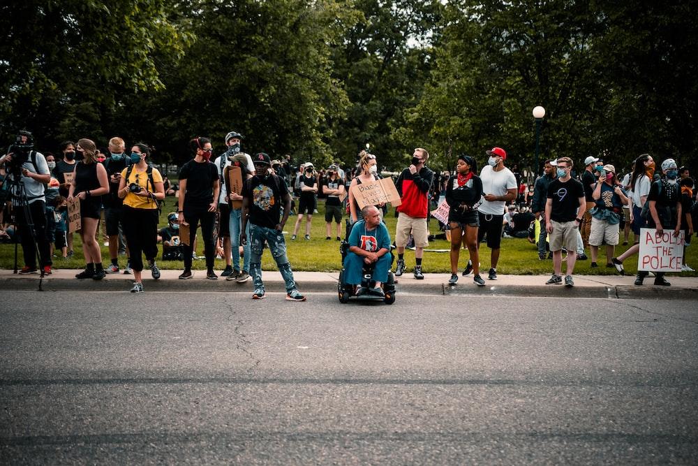 people standing on gray asphalt road during daytime