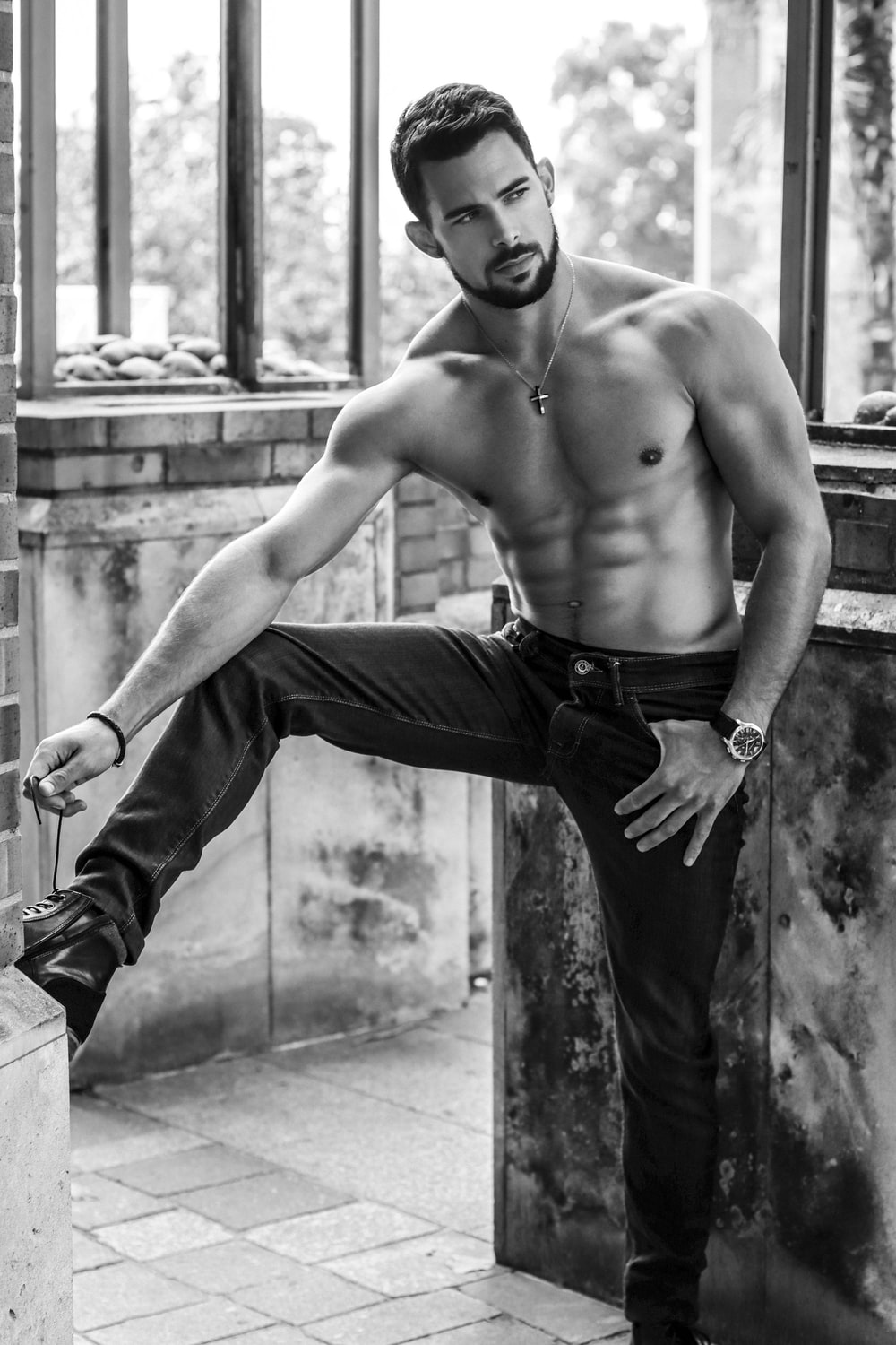 topless man in black pants and black leather boots