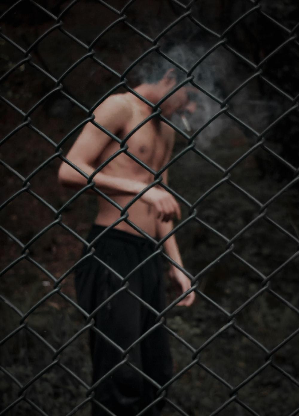 topless man in blue pants standing beside gray metal fence
