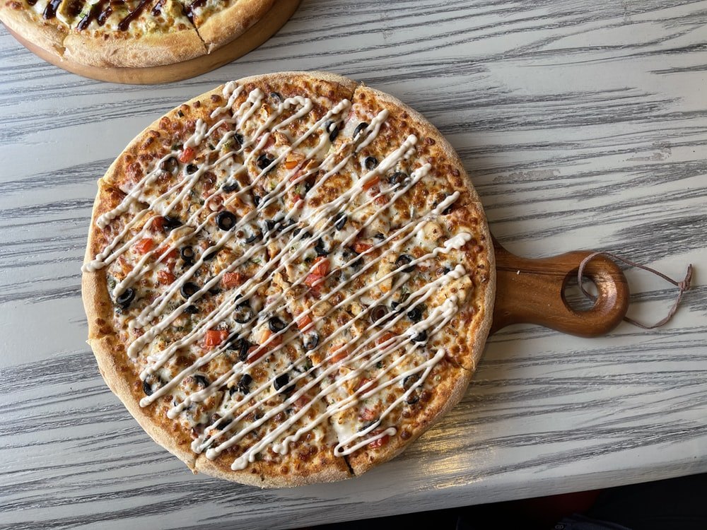 brown round pizza on brown wooden table