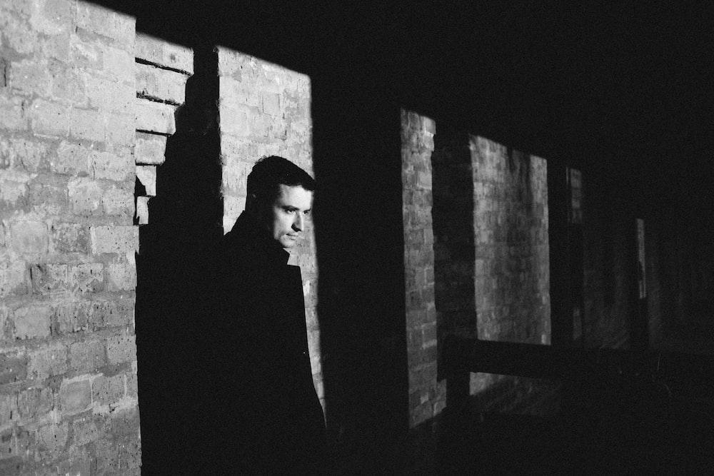 man in black suit standing near brick wall