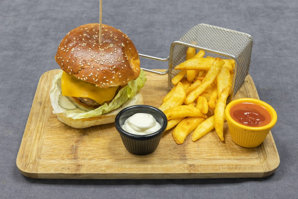 burger and fries on brown wooden chopping board