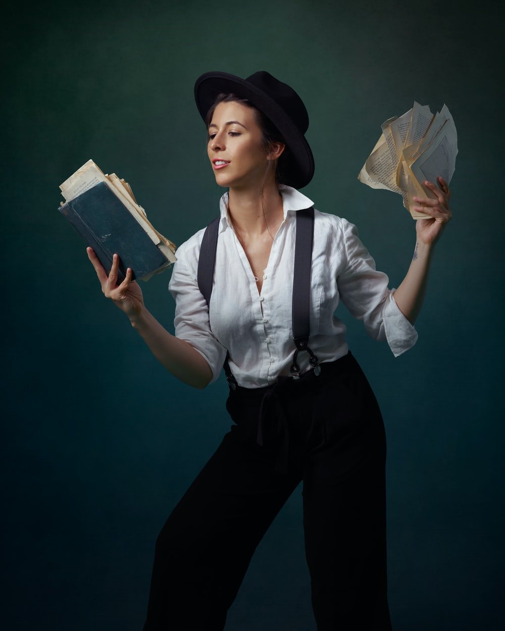 woman in white dress shirt and black pants holding white paper