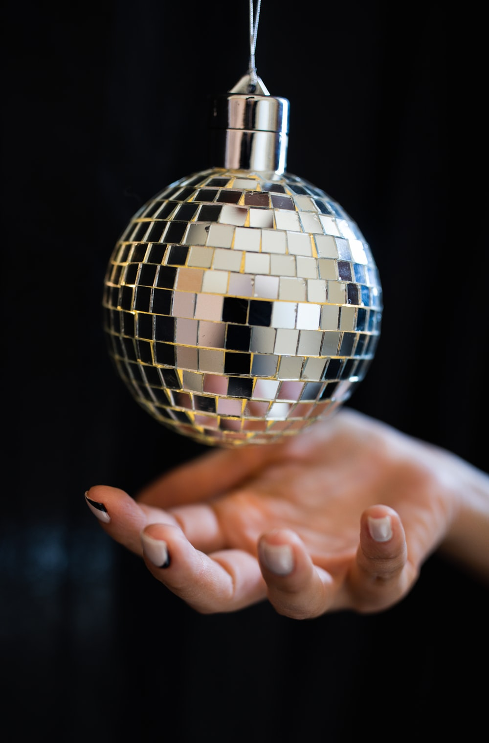 person holding silver and black ball