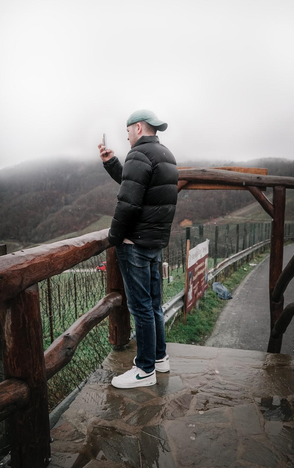 man in black jacket and blue denim jeans standing on bridge during daytime
