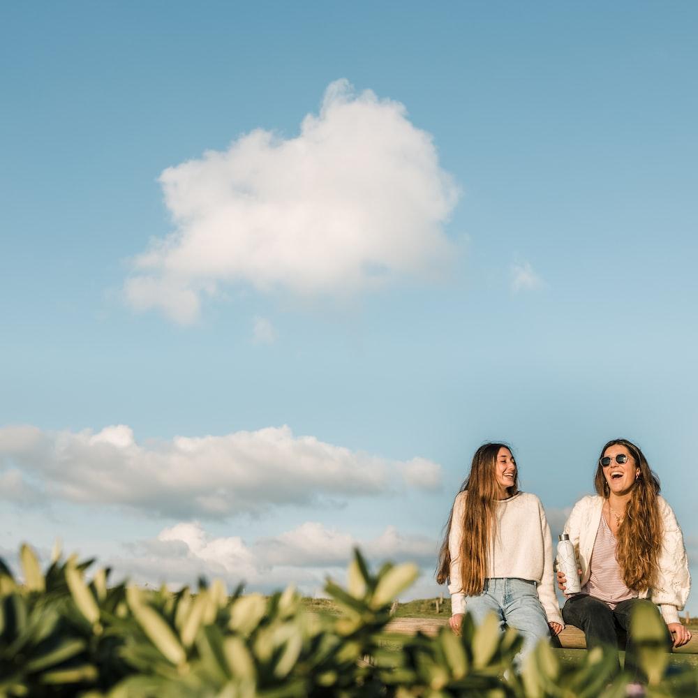 3 women standing on green grass field under blue sky during daytime
