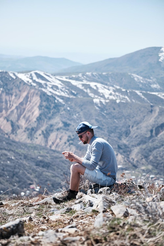 man in blue long sleeve shirt sitting on brown rock during daytime