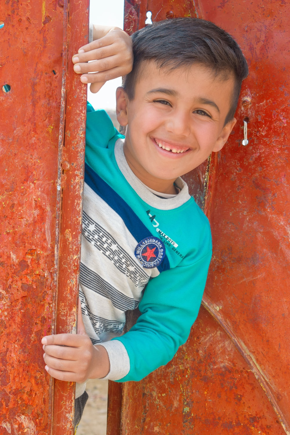 boy in red and blue long sleeve shirt smiling