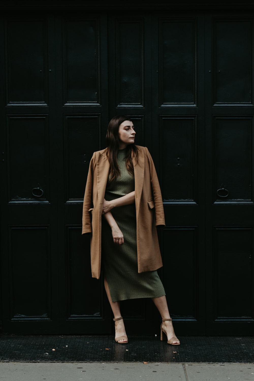 woman in brown coat standing beside black wooden door