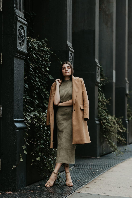 woman in brown coat standing near black metal gate during daytime