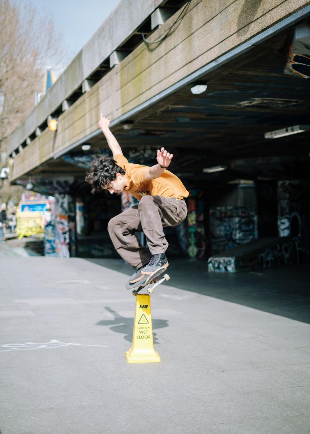 man in gray pants and black shirt doing skateboard stunts