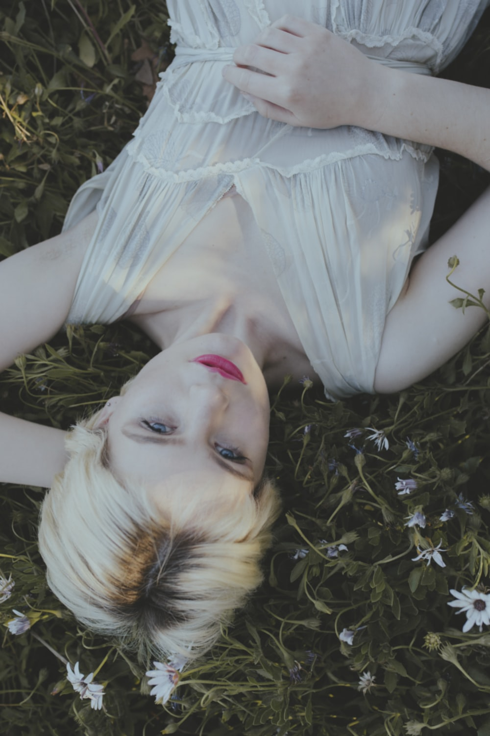 woman in white dress lying on green grass