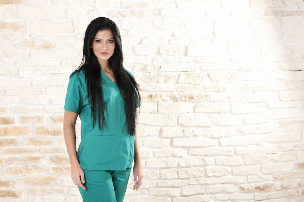 woman in green dress standing beside brick wall